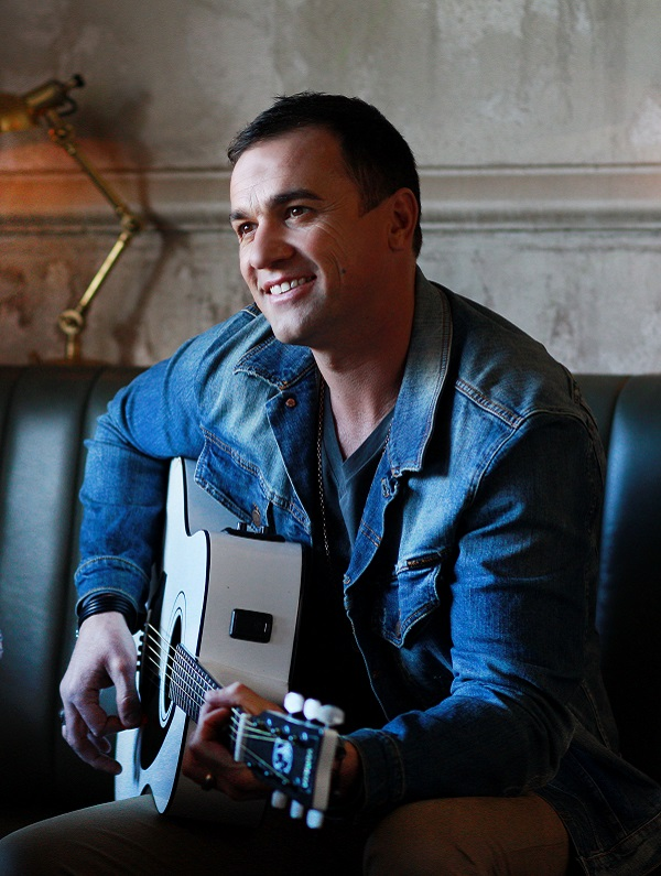 Shannon Noll playing guitar in portrait image